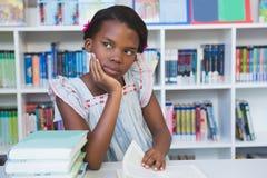 Scolara che si siede sulla tavola e sul libro di lettura in biblioteca Fotografia Stock Libera da Diritti