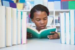 Scolara che si siede sulla tavola e sul libro di lettura in biblioteca Immagini Stock Libere da Diritti