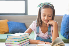 Scolara che si siede sulla tavola e sul libro di lettura in biblioteca Immagine Stock Libera da Diritti