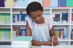 Scolara che si siede sulla tavola e sul libro di lettura in biblioteca Fotografia Stock