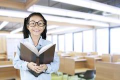 Scolara che sorride alla macchina fotografica con il libro in aula Fotografia Stock