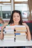 Scolara che sorride con i libri impilati allo scrittorio Fotografie Stock