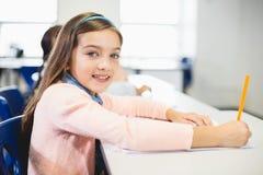 Scolara che sorride nell'aula Fotografie Stock Libere da Diritti