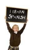 Scolara che sorride tenuta felice e allegra e lavagna di rappresentazione piccola con testo imparo lo Spagnolo Fotografia Stock Libera da Diritti