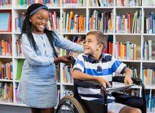 Scolara che sta con il ragazzo disabile sulla sedia a rotelle Fotografia Stock