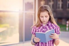 Scolara che studia all'aperto vicino alla scuola Fotografia Stock Libera da Diritti