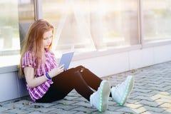 Scolara che studia all'aperto vicino alla scuola Fotografia Stock