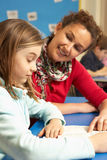 Scolara che studia nell'aula con l'insegnante Immagini Stock