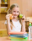 Scolara che tiene una mela e gli alimenti a rapida preparazione Immagine Stock
