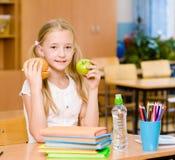 Scolara che tiene una mela e gli alimenti a rapida preparazione Fotografia Stock Libera da Diritti