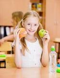 Scolara che tiene una mela e gli alimenti a rapida preparazione Fotografie Stock Libere da Diritti