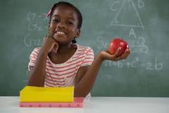 Scolara che tiene una mela rossa contro il fondo bianco Fotografia Stock Libera da Diritti