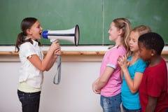 Scolara che urla tramite un megafono ai suoi compagni di classe Immagine Stock