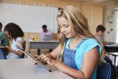Scolara che utilizza compressa nella classe della scuola elementare, fine su immagine stock