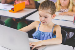 Scolara che utilizza computer portatile nell'aula Immagine Stock Libera da Diritti