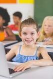 Scolara che utilizza computer portatile nell'aula Fotografia Stock Libera da Diritti