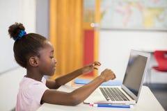 Scolara che utilizza computer portatile nell'aula Immagine Stock