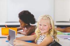 Scolara che utilizza la compressa di Digital nell'aula Immagine Stock Libera da Diritti