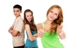 Scolara con gli amici che mostrano approvazione del segno Immagine Stock