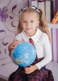 Scolara con il globo che si siede sulla tavola, raggiro di istruzione e della scuola Fotografia Stock