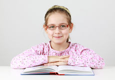 Scolara con il libro di lettura di vetro Immagine Stock