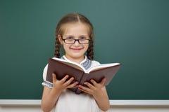 Scolara con il libro vicino al consiglio scolastico Fotografia Stock