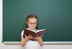 Scolara con il libro vicino al consiglio scolastico Immagini Stock