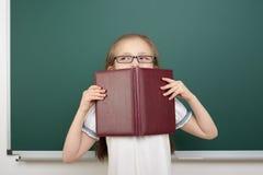 Scolara con il libro vicino al consiglio scolastico Fotografia Stock Libera da Diritti