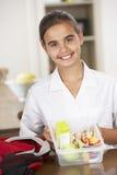 Scolara con il Lunchbox sano in cucina Fotografia Stock