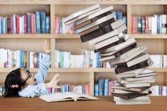 Scolara con il mucchio dei libri nella biblioteca Immagini Stock