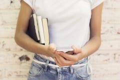 Scolara con il telefono cellulare ed i libri Fotografie Stock