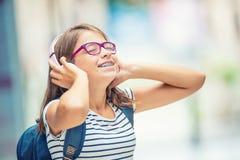 Scolara con la borsa, zaino Ritratto della ragazza teenager felice moderna della scuola con le cuffie e la compressa dello zaino  Fotografia Stock