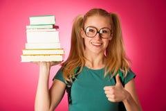 Scolara con la pila di libri e grande curiosi, impertinenti, allegri Immagini Stock