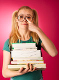 Scolara con la pila di libri e grande curiosi, impertinenti, allegri Immagine Stock Libera da Diritti
