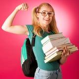 Scolara con la pila di libri e grande curiosi, impertinenti, allegri Fotografia Stock