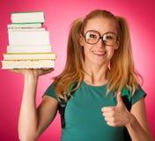 Scolara con la pila di libri e grande curiosi, impertinenti, allegri Immagini Stock Libere da Diritti