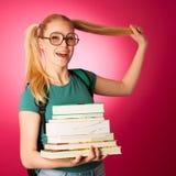 Scolara con la pila di libri e grande curiosi, impertinenti, allegri Immagine Stock