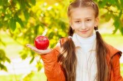 Scolara con le mele in autunno Immagine Stock