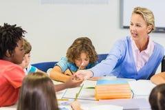 Scolara d'aiuto dell'insegnante con il suo compito in aula Fotografia Stock