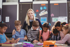Scolara d'aiuto dell'insegnante con il suo compito in aula Immagine Stock