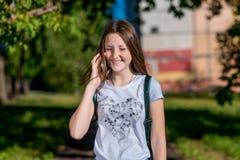 Scolara della bambina Estate in natura dopo le lezioni della scuola In sue mani tiene uno smartphone Conversazione sul telefono f Fotografia Stock Libera da Diritti