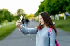 Scolara della bambina Estate in natura In mani che tengono uno smartphone che ascolta la musica sulle cuffie Catturi una maschera Fotografia Stock Libera da Diritti