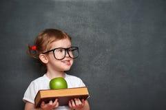 Scolara della ragazza con i libri e mela in un consiglio scolastico Immagini Stock Libere da Diritti