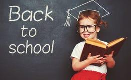 Scolara della ragazza con i libri in un consiglio scolastico Immagini Stock