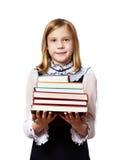 Scolara della ragazza con la pila pesante di libri Fotografia Stock Libera da Diritti
