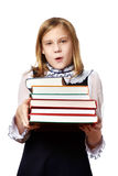 Scolara della ragazza con la pila pesante di libri Fotografia Stock