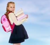 Scolara della ragazza con una cartella dietro le spalle ed i libri in Han Fotografie Stock