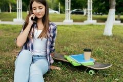 Scolara della ragazza dopo classe, sedentesi sull'erba, accanto ad una tazza dei manuali del pattino di tè Le chiamate dal telefo immagine stock
