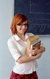 Scolara di Redhead davanti alla lavagna Fotografia Stock