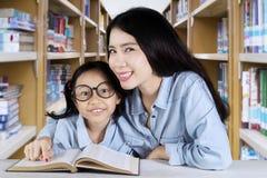 Scolara ed insegnante che sorridono nella biblioteca Fotografie Stock Libere da Diritti
